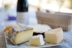 Photo of a cheese platter with a bottle of red wine in the background