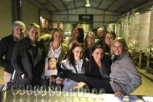 A group having a wine tasting in the wine vat room at Two Figs Winery